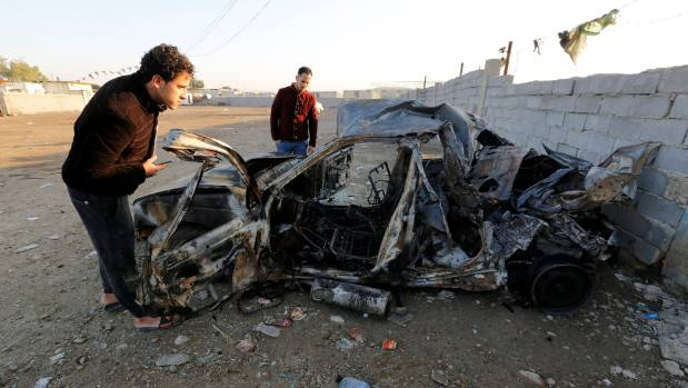 Men look at the wreckage of a burnt car after a suicide bomber detonated a pick-up truck in Sadr City, a heavily ...