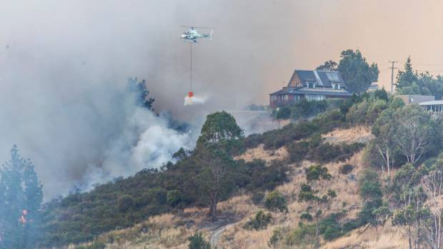 A helicopter uses a monsoon bucket to battle the blaze.