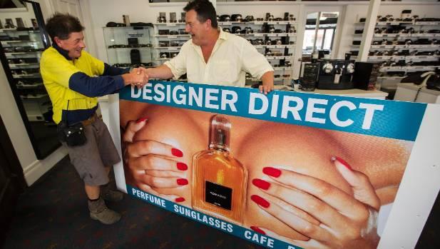 Designer Direct's infamous billboard has been sold. Designer Direct owner Michael Adams hands over to new owner Tim Harris.