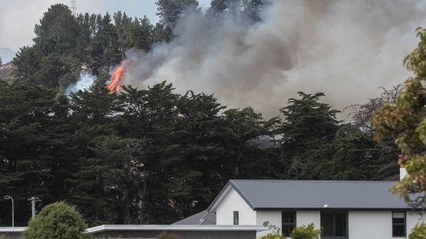 A fire burns above homes in Cracroft.