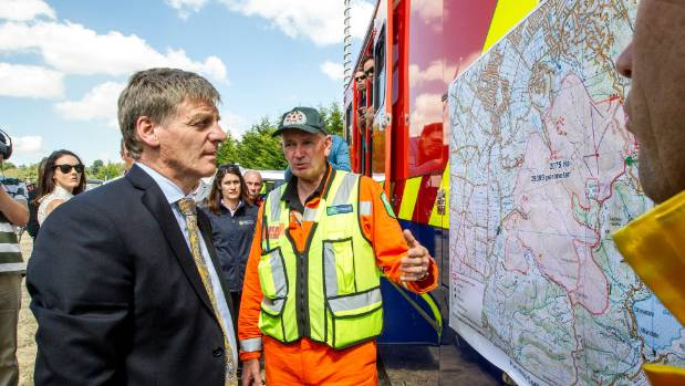 Prime Minister Bill English is briefed by workers at the Port Hills fire command centre in Christchurch.