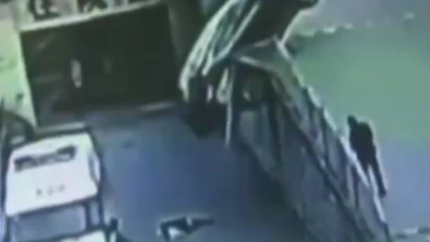 A mum lies on the ground after being hit by the SUV which is threatening to topple back and squash her.