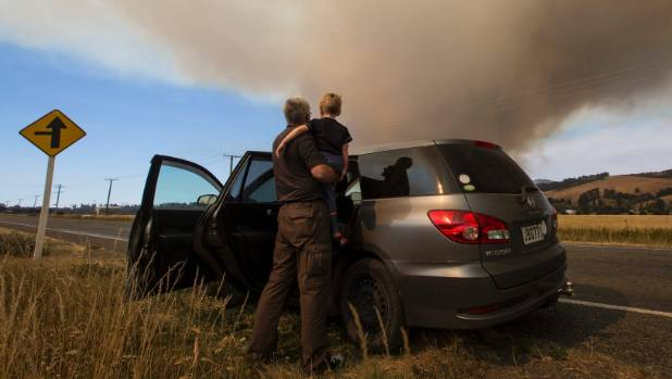 David and Michael Chadwick, 3, watch the Port Hills fire from State Highway 75 on Wednesday.