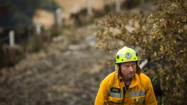 Bruce Webster of DOC works on the smouldering burnt remains of properties from the recent fires near Worsley Rd, Port ...