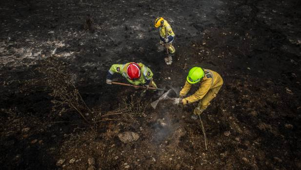 St Albans fire crews and DOC staff work on the smouldering burnt remains of properties from the recent fires near ...