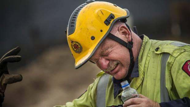 St Albans firefighter Keys Kerdemelidis-Kiesnowski rinses his smoke-filled eyes.