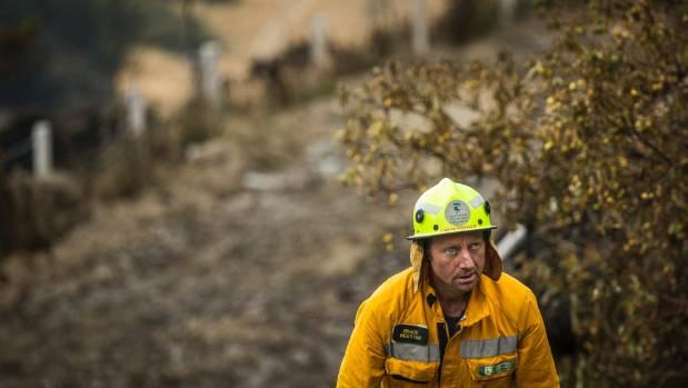 DOC's Bruce Webster works on the smouldering burnt remains of properties.