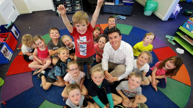 Myross Bush School principal Jamin Lietze with star of the video Flynn McGregor, 5, standing, and the rest of his class. ...