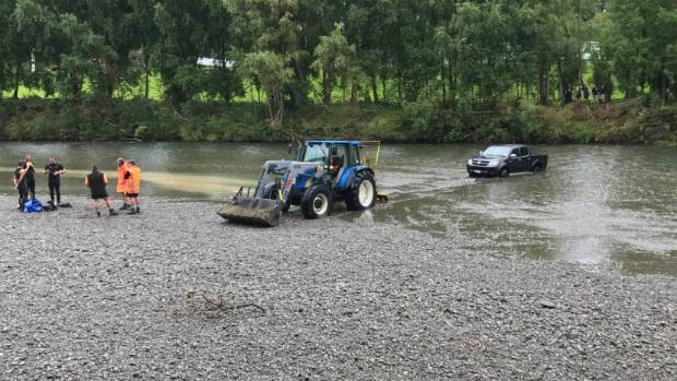 The ute being dragged out of the river.