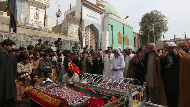 Men and relatives gather to attend funeral prayers for victims killed in a suicide blast at the tomb of Sufi saint Syed ...