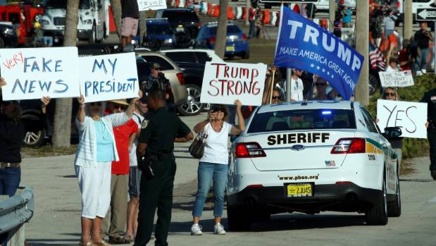 Signs are held aloft as the motorcade of U.S. President Donald Trump drives through West Palm Bech, Florida.