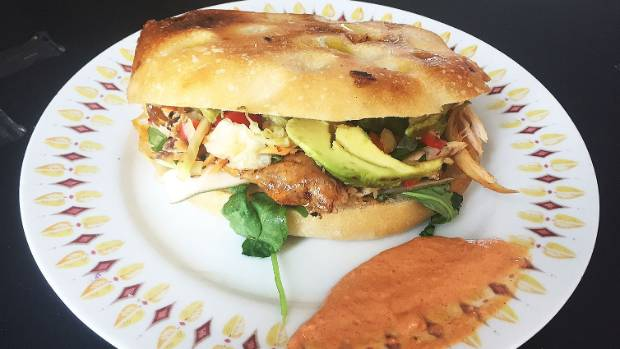 The chicken deluxe sandwich is packed with veges.