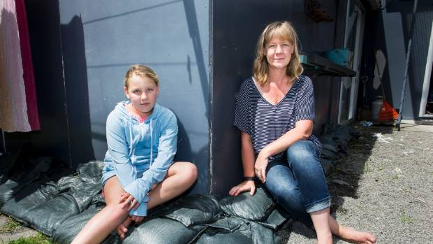 Otaki resident Tanja Gerritsen, pictured with daughter Kate Osborne, sits on sandbags which permanently decorate her backyard. — Photograph: Maarten Holl.