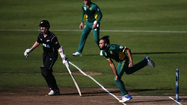 Imran Tahir of South Africa bowls as Kane Williamson of New Zealand looks on.