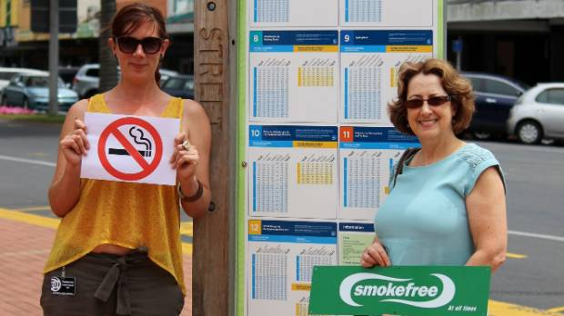 RLC staff Rachel Doelman (left) and Rosemary Viskovic with smokefree signage at Arawa Street bus stop.