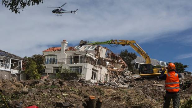 A house is demolished on the cliff side above Redcliffs. Some red-zone demolitions in the Port Hills have cost $300,000.