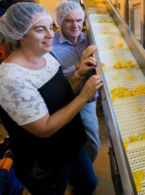 Heartland Potato Chips general manager Charlotte Bowan, and Heartland owner Raymond Bowan watch the cooked chips as they ...