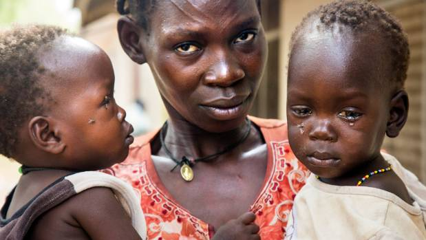 Flora Fai holds her twins, (left to right) Kegi and Yada Jacob, both with malnourishment, at the malnutrition ward in Al ...