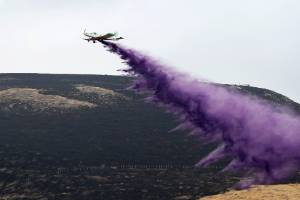 Robinson sprays fire retardant on the hill above Kennedy's Bush during his efforts to help fight the Port Hills fire.