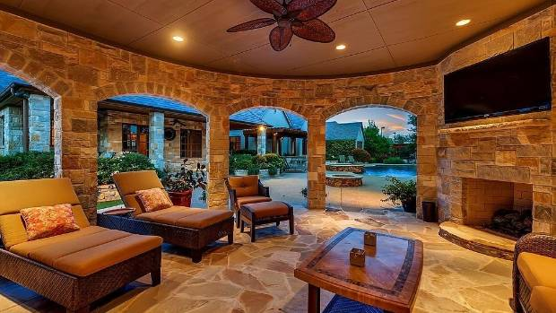 The resort-style home has a grand outdoor entertaining area equipped with an outdoor living room and kitchen.