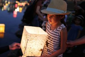 A girl holds a candle lit paper lantern as she floats it on the river during 71st anniversary activities, commemorating ...