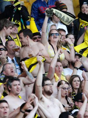 The Wellington Phoenix's Yellow Fever supporters group partake in their traditional shirts off celebration in 2014.