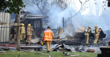 Firefighters douse a shed fire that resulted in a man being hospitalised with burns to his arm.