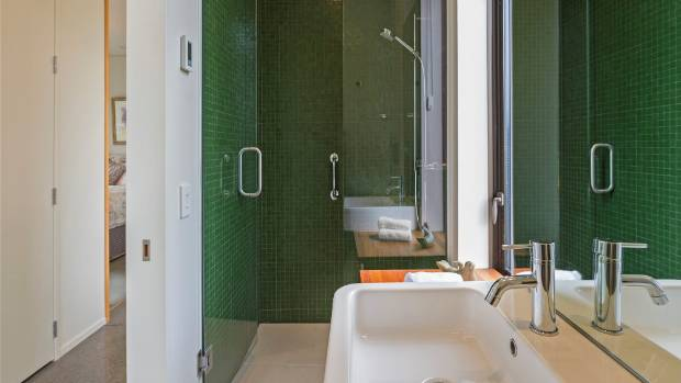 Green mosaic tiles define the second bathroom.