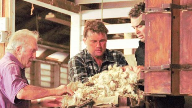 Jack Roberts, left, and his son Alan Roberts from Timahanga, centre, load wool into the mini pocket press with Alan's ...