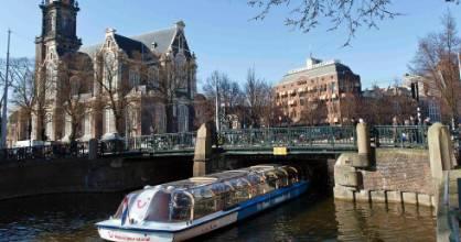 A tourist boat passes under a bridge next to the Westerkerk church.