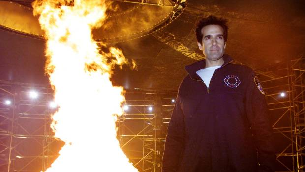 """Copperfield poses in front of a """"Tornado of Fire"""", to promote a stunt in 2001."""