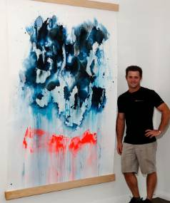 Luke Dell of Nelson City Framers & Gallery, with a work from Lance Kerr's exhibition Logic of Sense.