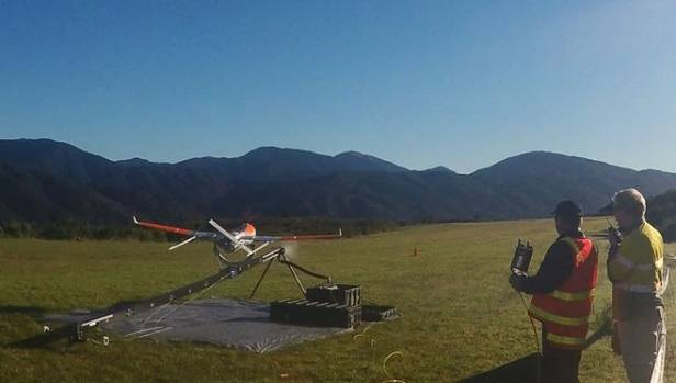 Flight crew members launch a drone aircraft  during a trial flight inspecting Transpower's transmission lines in the ...