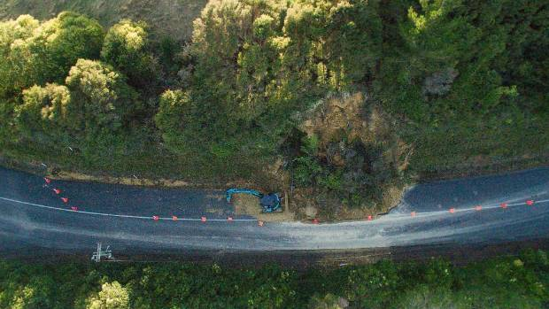 Workers attempt to clear a slip on the road to Hunua Falls in the Clevedon area after flooding on Wednesday.