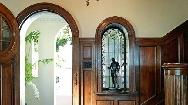 Original oak panelling was restored in the entranceway; archways are a signature feature of Spanish Mission homes.