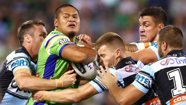 Joseph Leilua of the Raiders is surrounded by Cronulla Sharks players in the tackle.