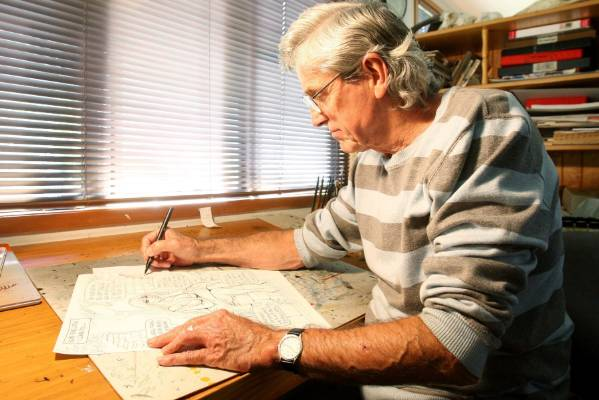 Cartoonist Murray Ball at his desk at his Gisborne home.