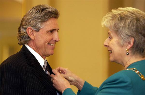 Murray Ball receives his investiture from Dame Silvia Cartwright at Government House in 2002.