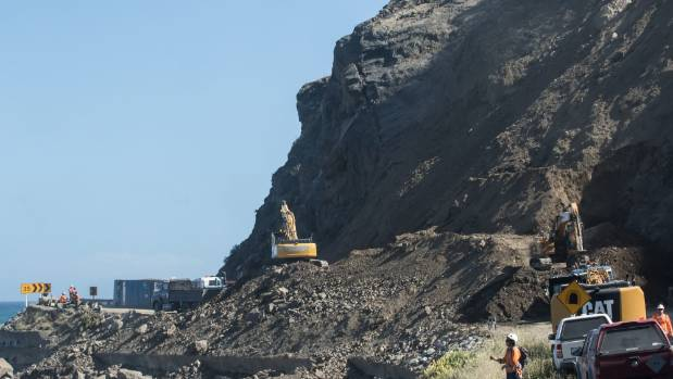 An excavator works to clear slips south of Kaikoura following the November earthquake.
