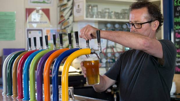Barman Steve Major pours a low alcohol 4 percent Three Piece Wheat beer at The Free House. The pub offers about a dozen ...