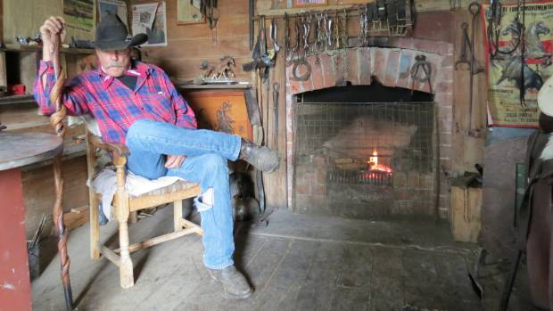 John Kimber rests by the fire in the more than 100 year old heritage hut.
