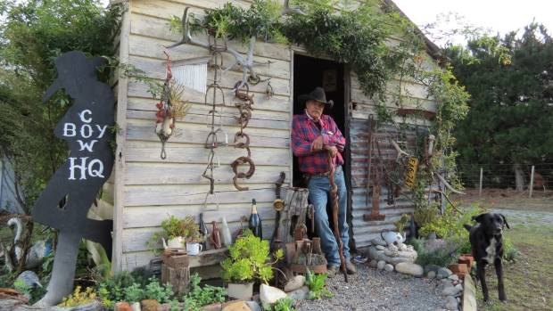 Professional cowboy John Kimber leans at the entrance of the heritage hut.