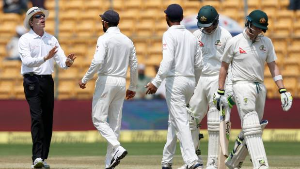 Virat Kohli hastily speaks with an umpire as Australia's Steven Smith walks off the ground after being dismissed in the ...