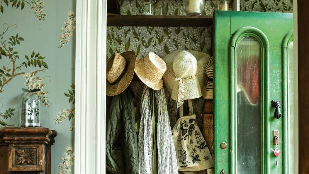 Old hats hang on the original hall hooks; Bronwyn chose Lily of the Valley Sandberg wallpaper for the entry porch.