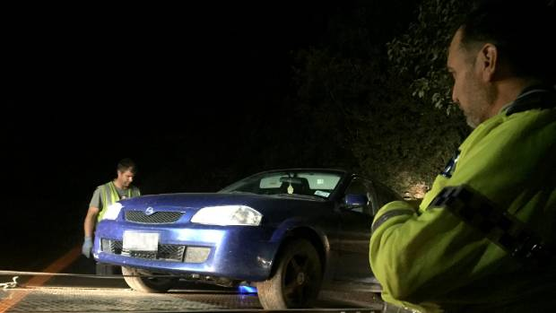 A police sergeant looks on as a recovered car is towed away from outside Masterton's Colin Pugh Sports Bowl.