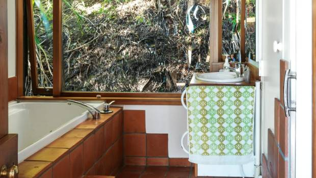 The main bathroom looks towards the cliff, which is lit by night and bathed in dappled light by day.