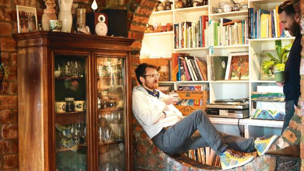 Nigel finds the circular entry to the library nook a perfect place to perch; on top of an antique bureau bookcase is ...