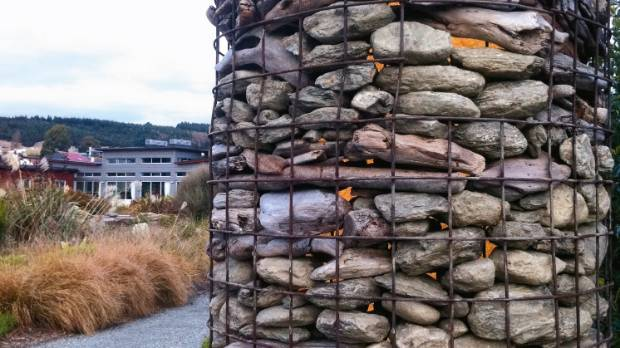 A stone and driftwood column marks the entrance to a Wanaka property and creates a focal point in the landscape.