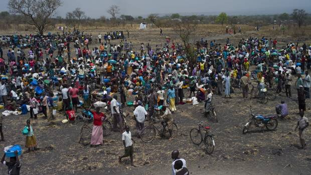 Refugees queue at a World Food Programme (WFP) food distribution site at a refugee settlement on February 25, in ...