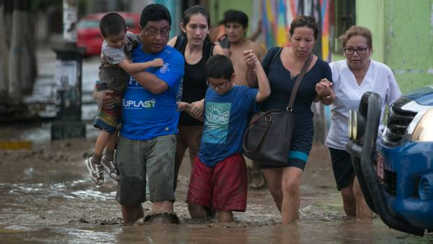 Residents cross a flooded street in Trujillo, in northern Peru.